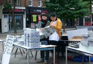 Two women read Fitzrovia News at a stall in Whitfield Gardens
