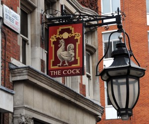 Pub sign wth cock on it and outside of pub showing large glass lanterns