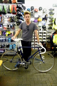 Ewan McGregor standing in bicycle shop with fixed-gear bicycle