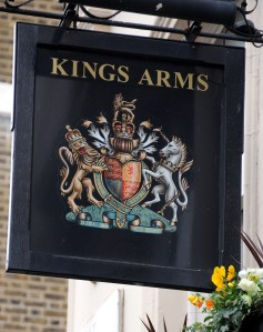 Sign showing coat of arms outside Kings Arms pub.