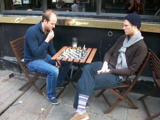 Two men sitting down playing a game of chess.
