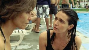 A scene at a poolside where two women look at each other.