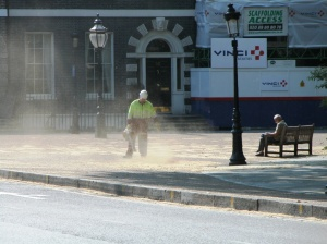Man using leaf blower and dust cloud rising.