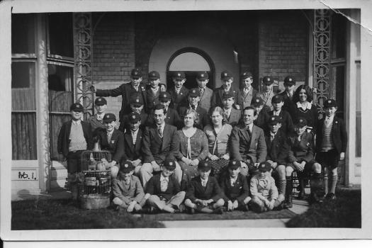 Group of school boys posing for photograph on steps of hotel.