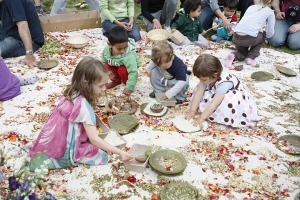 Children on a carpet making mandalas.