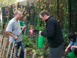 Adults and children in garden palting bulbs.