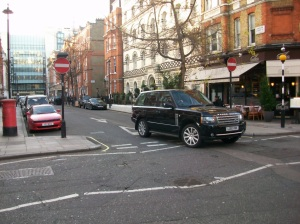 A Range Rover turning a corner in a narrow street.