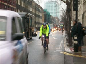 A cyclist riding in heavy traffic.