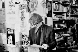 Man standing reading in bookshop.