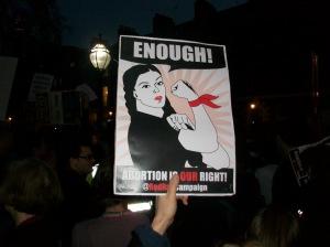 """A placard reads """"enough!""""."""