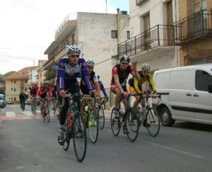 Group of cyclists riding through Spanish village.