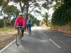 Two women rider bicycles along orange grove road.