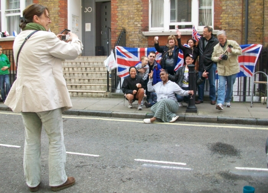 A photographer taking a picture of a group of people in the street.
