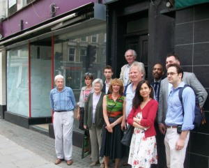 Group of people standing outside Georgian building.