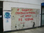 Banksy artwork on wall saying: If Graffiti Changed Anything.