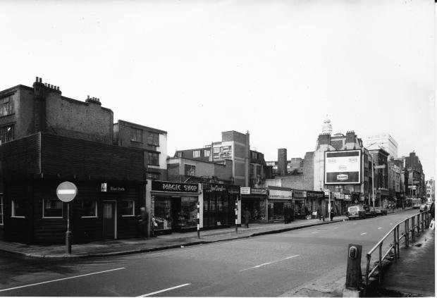 Blue Posts pub and single storey buildings along Tottenham Court Road.