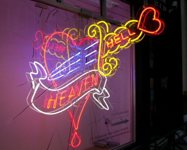 Neon light art dagger through window.