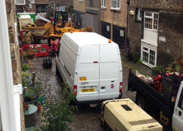 Vehicles in cobbled mews.