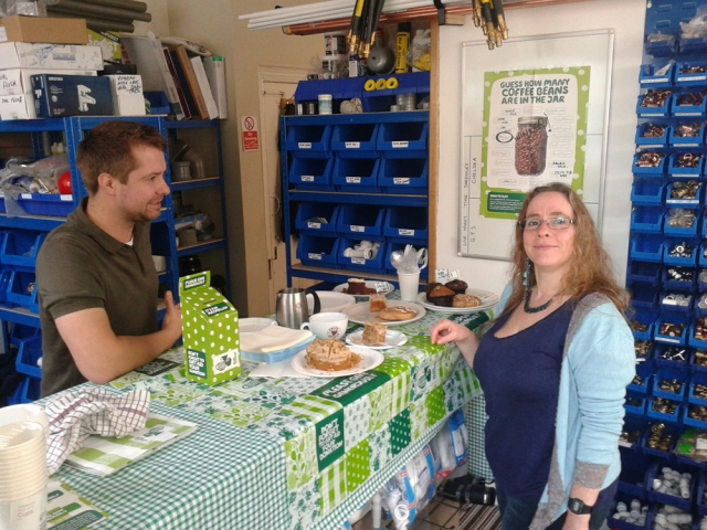 Man and women at coffee morning in plumbing shop.