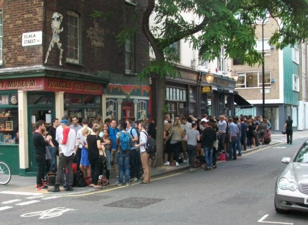 Crowds of people drinking on the pavement outside pub.