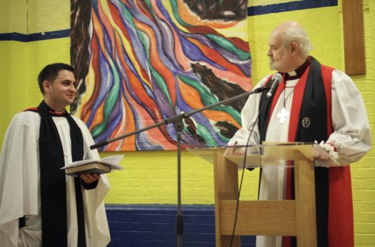 Vicar and Bishop standing in hall.