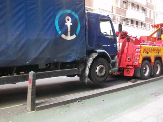 Lorry being towed away after crashing into bollard.