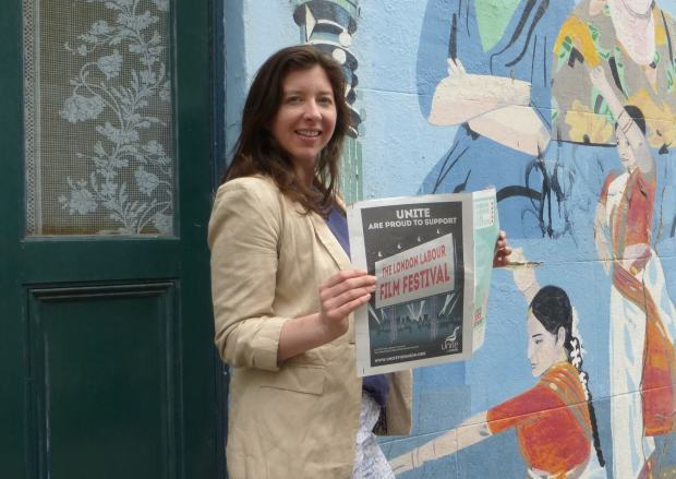 Woman standing with film programme in front of mural.