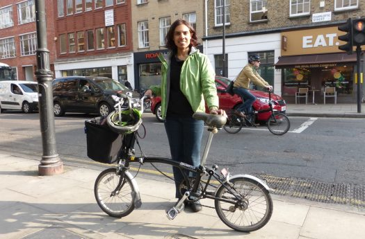 Woman standing with folding bicycle.