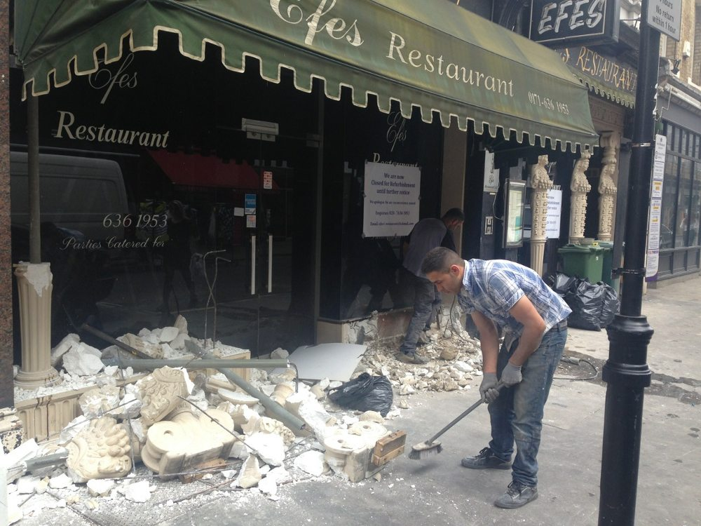 Builders demolishing front of restaurant.