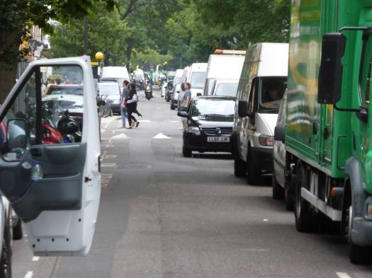 Cars and vans queuing in street.