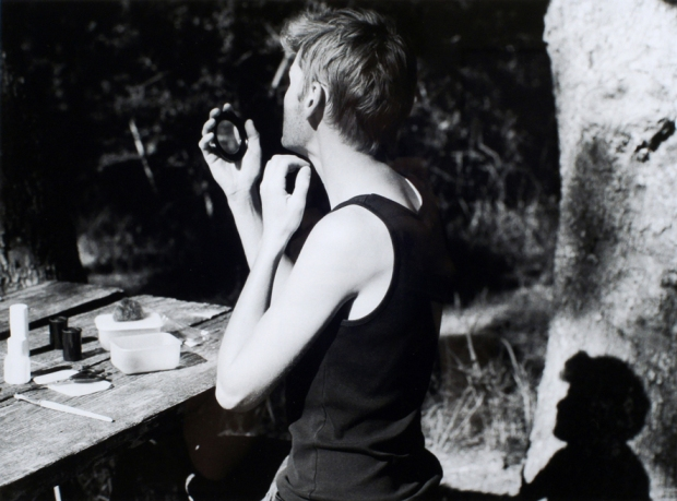Black and white photograph of man looking into a mirror.