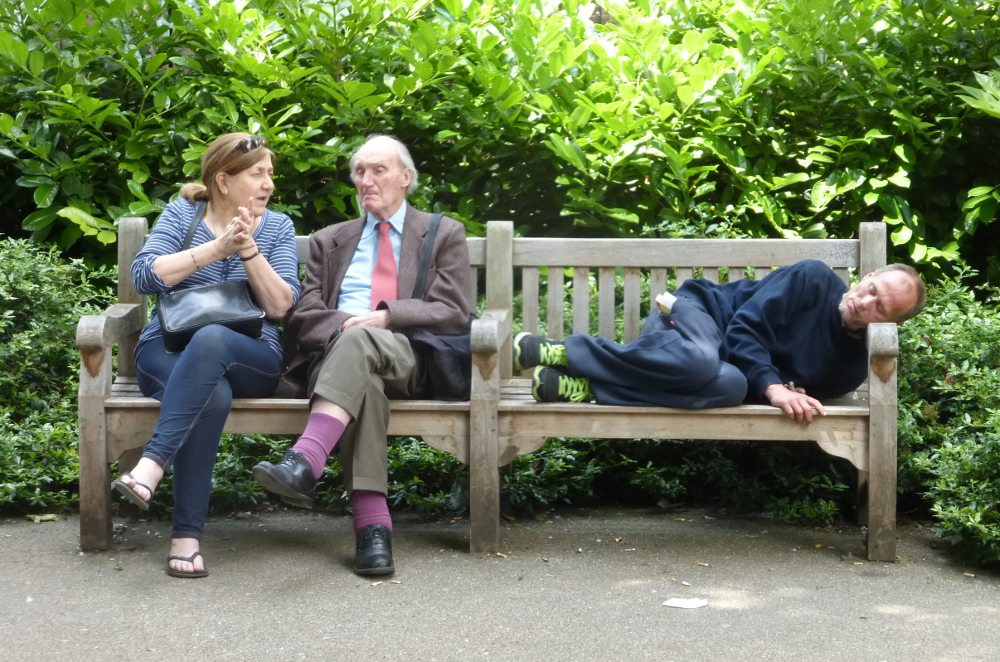 Three people share a wooden bench.