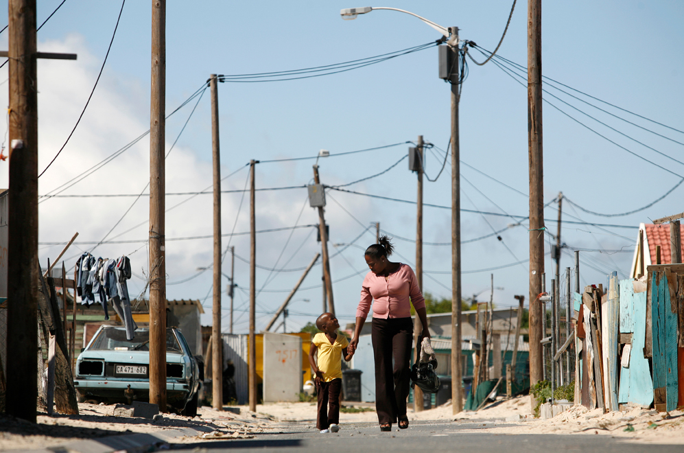 Woman and child walk along street.