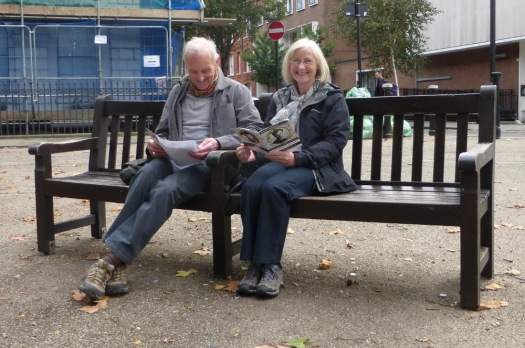 Man and woman sitting on bench in square.