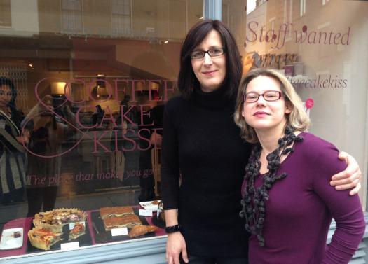 Two people outside shopfront.