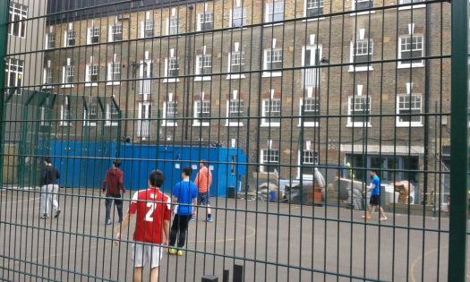 Young men playing football on 5-aside pitch.
