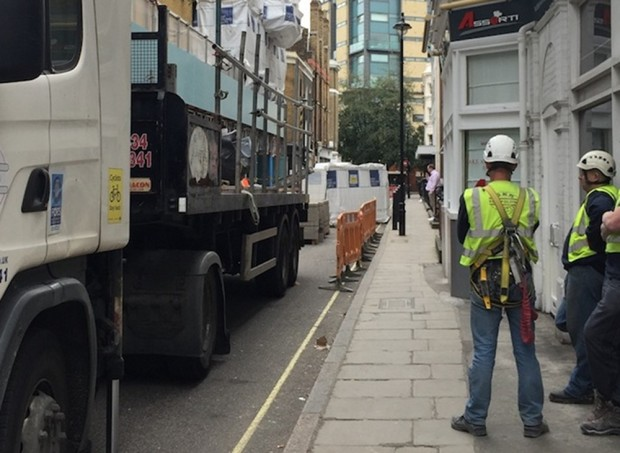 Building workers standing next to lorry.