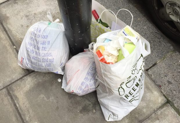Refuse in bags on pavement.