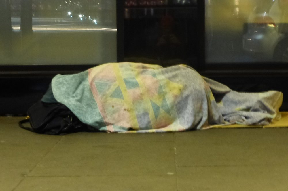 Woman sleeping on the pavement.
