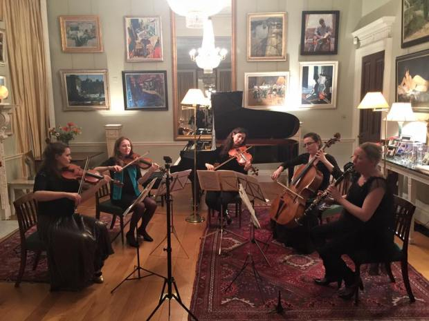 String musicians sitting in a room playing their instruments.