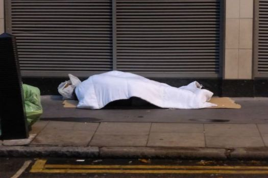 Rough sleeping on pavement.