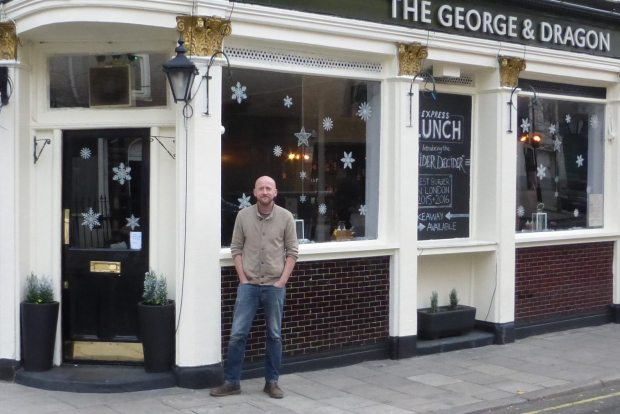 Man standing outside pub.