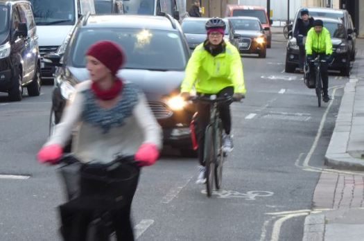 Cyclists travelling along London street.