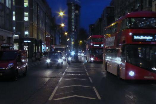 Motor traffic in street at night.