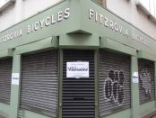 Shop front with roller shutters down.