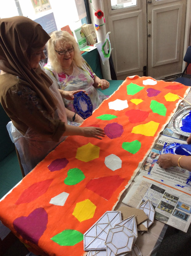 Women around table working on art project.