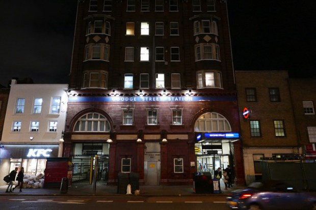 Front of tube station at night.