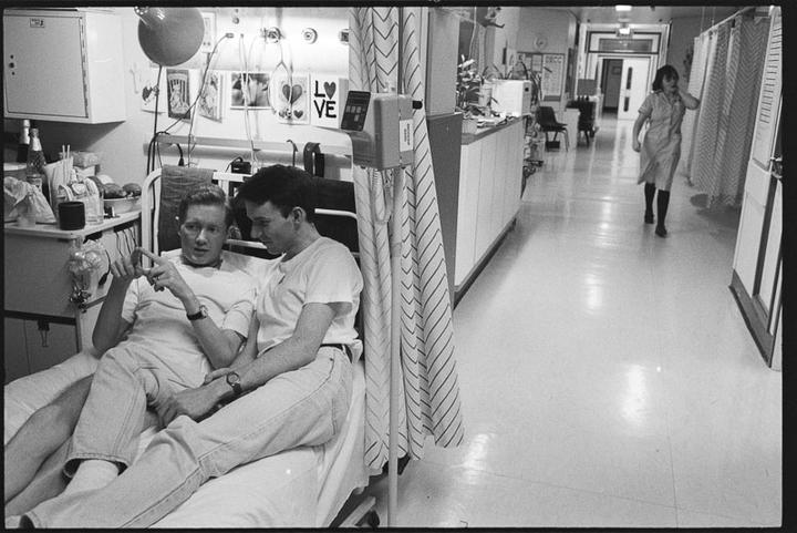 Two men on a bed in hospital ward.
