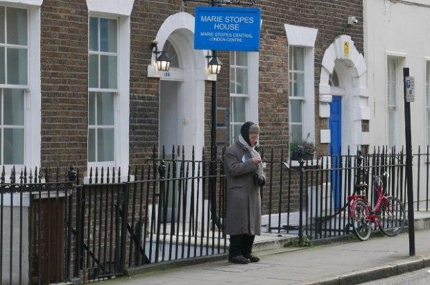 Man standing outside women's clinic.
