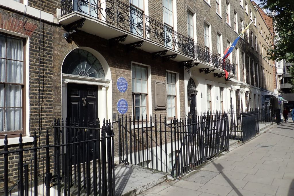 Row of buildings showing blue plaques.